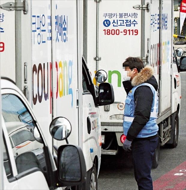 쿠팡 물류센터 직원이 서울 쿠팡 서초1 배송캠프에서 배송트럭 기사와 대화하고 있다.  연합뉴스