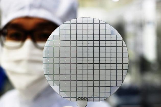 (사진) 예스파워테크닉스 관계자가 칩 제조공정이 완료된 웨이퍼를 들어 보이고 있다. /SK(주) 제공