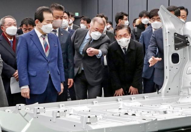 (사진) 정의선(가운데) 현대자동차그룹 회장이 2월 18일 경기 화성시 현대차 남양기술연구소에서 정세균(왼쪽) 국무총리, 성윤모(오른쪽) 산업통상자원부 장관에게 전기차 전용 플랫폼(E-GMP)에 대해 설명하고 있다. 한국경제신문