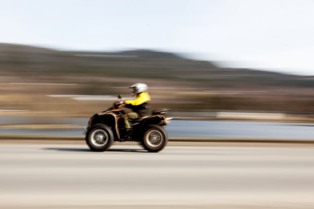 A quad on a road with motion blur