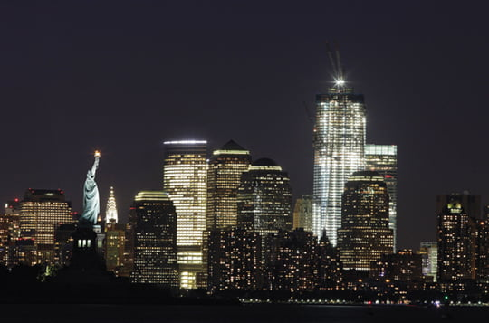 In this Aug. 23, 2011 file photo, One World Trade Center rises above the Manhattan skyline and the Statue of Liberty, in New York. The tower will be 104 floors and 1,776 feet (541 meters) tall when completed. Ten years after terrorists destroyed the World Trade Center, the new World Trade Center is rising from ground zero. (AP Photo/Mark Lennihan, File)