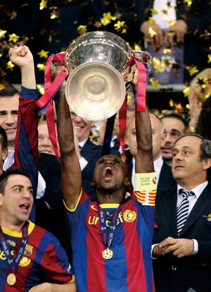CORRECTS NAME OF PLAYER - Barcelona's Eric Abidal lifts the cup after winning the Champions League final soccer match against Manchester United at Wembley Stadium, London, Saturday, May 28, 2011. (AP Photo/Jon Super)/2011-05-29 10:40:28/
