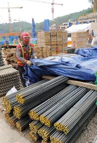 철근값이 천정부지로 치솟고 있는 가운데 은평뉴타운 2지구의 한 건설현장에서 인부가 27일 비가 올것에 대비해 철근을 천막으로 덮고 있다.  /허문찬기자  sweat@  20080527