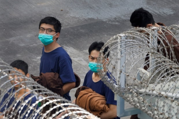 철조망 뒤로 갇혀 있는 홍콩 민주화 운동가 조슈아 웡. 사진=연합뉴스