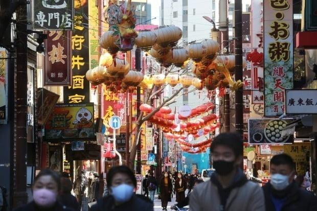 일본 가나가와현 요코하마에서 시민들이 마스크를 착용한 채 차이나타운 거리를 걸어가고 있다.(사진=AP=연합뉴스)