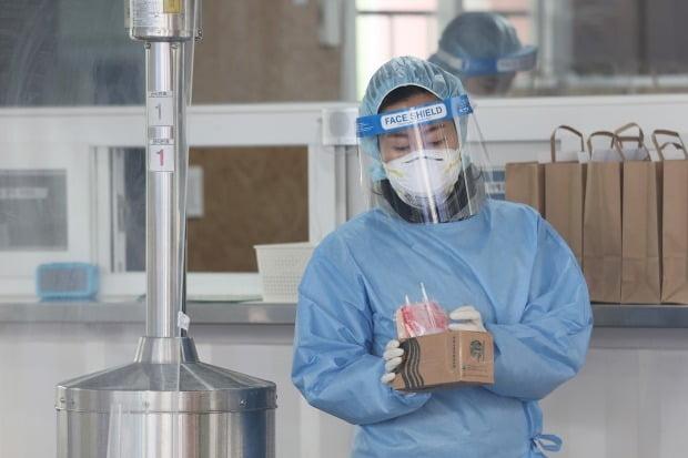 서울 동작구보건소에 마련된 선별진료소에서 의료진이 검체채취 키트를 들고 있다. 사진=연합뉴스