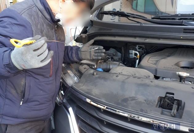 한 차량 정비사가 딥스틱을 꺼내 엔진오일 상태를 확인중이다./ 사진=신현아 한경닷컴 기자