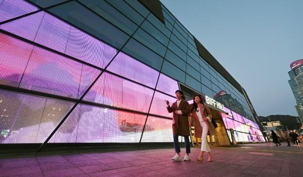 LG전자가 부산 해운대구 소재 영화의전당 유리벽에 206제곱미터 규모 투명 LED 필름을 설치했다. 투명 LED 필름이 설치된 영화의전당 외벽은 낮에는 투명한 일반 유리창처럼 보이지만 저녁에는 영화 명장면을 보여주는 스크린이 된다. LG전자 모델들이 투명 LED 필름이 설치된 영화의전당 주변 경관을 소개하고 있다/사진제공=LG전자