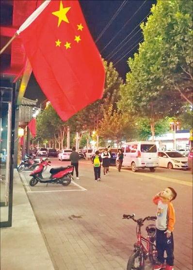 중국 베이징 시내에서 네 살 소년이 한밤중에 오성홍기에 경례하고 있다.   푸른역사 제공
