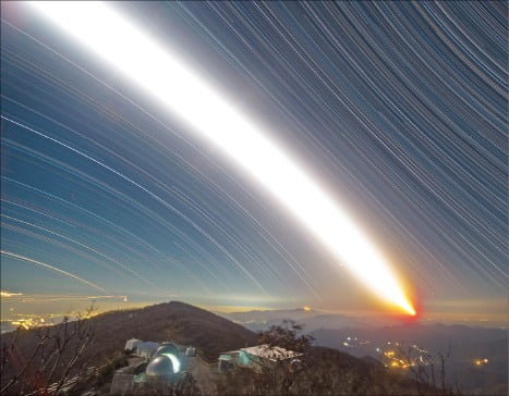 왼쪽 아래 불 켜진 돔에 원격 관측 망원경이 있고, 그 위로 달이 지난 모습. 서쪽으로 지는 순간까지 약 7시간 노출한 영상을 모은 것이다.  /전영범