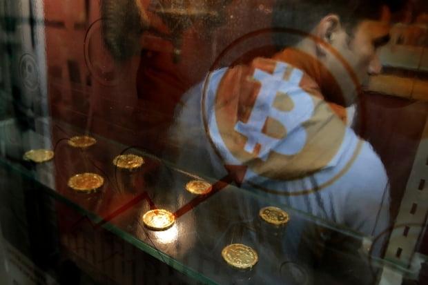 홍콩의 한 시민이 2017년 12월 비트코인 자동입출금기(ATM)를 이용하는 모습. AP연합뉴스