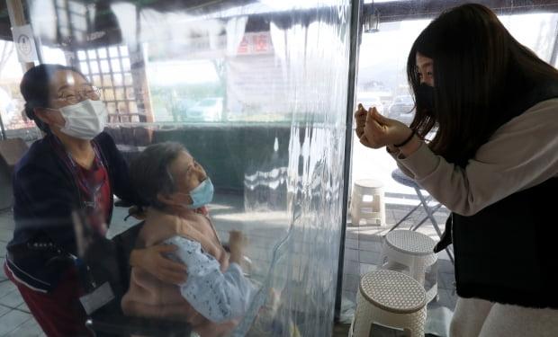 지난달 12일 울산시 울주군 이손요양병원에 설치된 비닐 면회실에서 며느리가 비닐막 너머 앉은 시어머니에게 손하트를 만들어 보이고 있다./사진=뉴스1