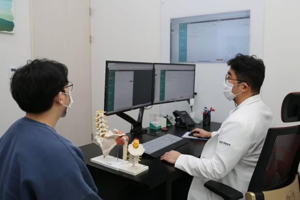 정종훈 힐링본정형외과 원장이 엣지앤넥스트를 사용해 환자를 진료하고 있다.