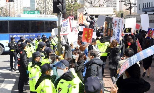 양부모 학대로 숨진 '정인이 사건' 4차 공판이 열린 17일 오후 서울 양천구 남부지방법원 앞에서 시민들이 양모가 탄 호송차량을 향해 항의하고 있다. 2021.3.17/뉴스1
