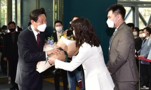 오세훈 서울시장이 8일 서울 중구 서울시청에 발을 들이자 직원들이 축하 꽃다발을 전달하고 있다. 연합뉴스
