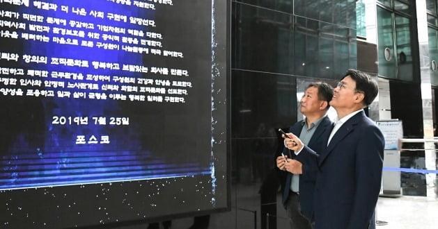최정우 포스코 회장(오른쪽)이 지난해 7월28일 서울 대치동 포스코센터에서 열린 '기업시민헌장 미디어아트' 제막식에서 이이남 작가에게 헌장 내용을 설명하고 있다.  포스코 제공