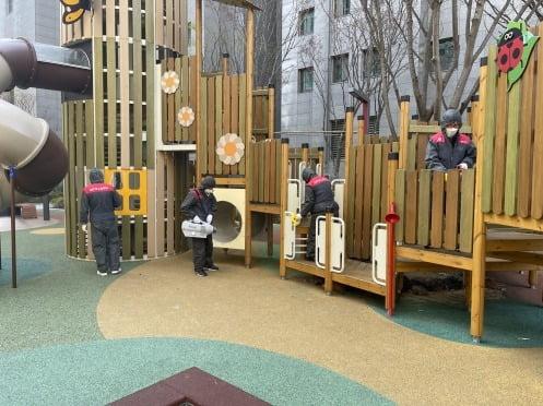 롯데건설이 고덕 롯데캐슬 베네루체 아파트의 어린이 놀이터를 방역 중이다.