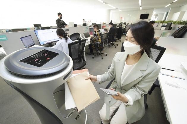 KT가 KT 서울 광화문 이스트 사옥에서 임직원을 대상으로 'AI로봇 우편배송 서비스'를 시작했다고 18일 밝혔다. 사진은 임직원이 'AI로봇 우편배송 서비스'를 이용하는 모습. 2021.4.18 [사진=KT 제공]