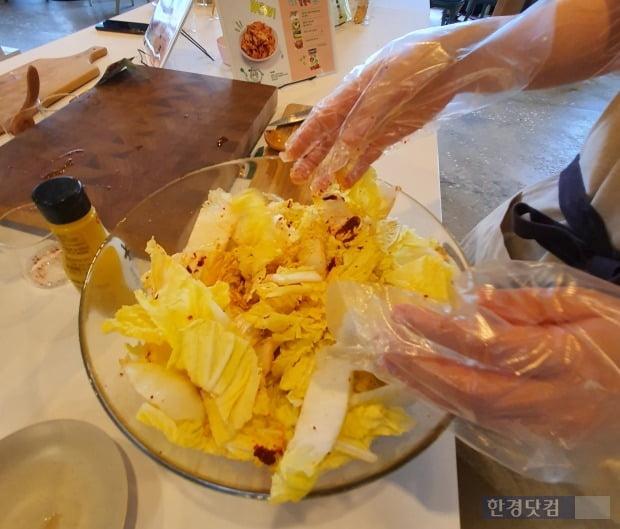 '겉절이 소스' 1포와 고춧가루 40g을 섞어 김치 양념을 완성한 뒤 먹기 좋은 크기로 자른 알배추 한 포기(750~800g)를 양념과 버무리는 모습. [사진=이미경 기자]