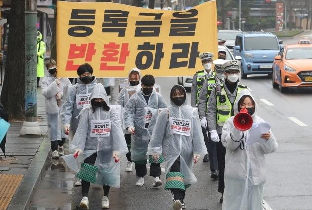 2021 등록금반환운동본부 관계자들이 지난달 서울 종로구 경복궁역 인근에서 코로나19 비대면 수업 여파로 인한 대학 등록금 반환을 촉구하는 삼보일배를 하고 있다.