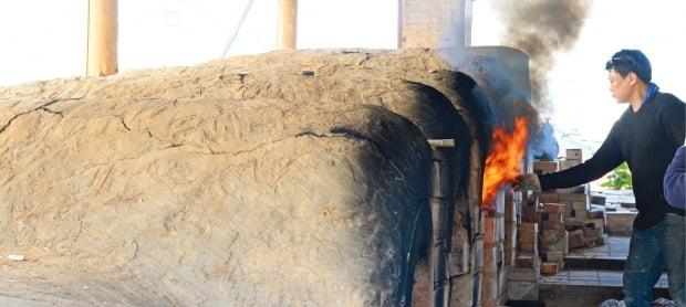 이천도자예술마을 안에 있는 가마에서 한 도예인이 소성작업을 하고 있다. 도자예술마을의 도예인들은 아직도 흙가마에 나무로 도자를 구워내는 전통방식을 선호한다.