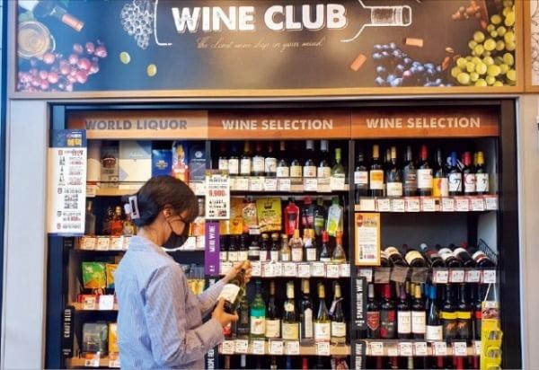 '홈술' 열풍으로 집 근처 '슬세권'에 와인 로드숍이 늘어나고 있다. 한 소비자가 편의점 이마트24 와인 전문 코너에서 와인을 고르고 있다.  이마트24 제공