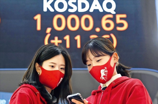 < 이게 얼마만이야 > 12일 코스닥지수가 2000년 9월 14일(1020.70) 후 20년7개월 만에 1000선을 넘어섰다. 서울 여의도 한국거래소에서 직원들이 스마트폰으로 코스닥지수를 확인하고 있다.  허문찬 기자 sweat@hankyung.com