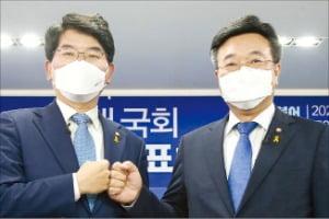 더불어민주당 박완주 의원(왼쪽)과 윤호중 의원이 15일 원내대표 후보자 합동토론회에서 주먹 인사를 하고 있다. 김범준 기자 bjk07@hankyung.com