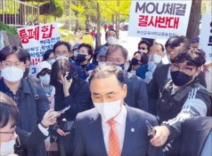 차정인 부산대 총장(가운데)이 19일 부산교대 본관 앞에서 부산교대 총동창회의 통합 MOU 반대 시위에 막혀  되돌아가고 있다.  연합뉴스
