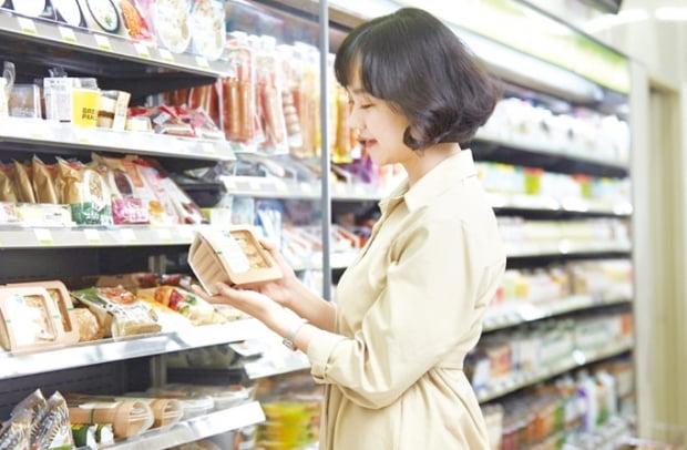 편의점 CU를 찾은 한 고객이 친환경 케이스에 담긴 샌드위치를 살펴보고 있다.    BGF리테일 제공