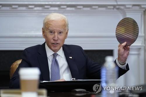 조 바이든 미국 대통령이 12일(현지시간) 백악관에서 열린 반도체 관련 화상회의에서 반도체를 들어보이고 있다.[AP]