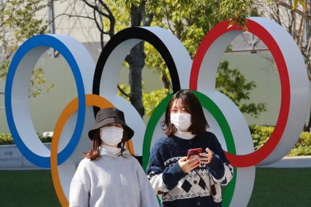 일본 도쿄에서 행인들이 오륜 조형물 앞을 지나가고 있다. 사진=AP