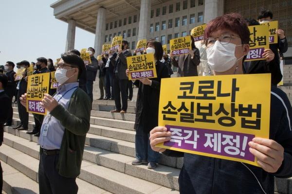 정의당 당원들이 지난 19일 국회의사당 앞 계단에서 열린 코로나 손실보상법 소급적용 제정 촉구 기자회견에서 피켓을 들고 있다. /사진=뉴스1