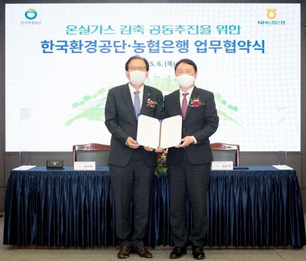권준학 농협은행장(오른쪽)이 6일 서울 중구 농협은행 본사에서 장준영 한국환경공단 이사장과 온실가스 감축 공동추진을 위한 업무협약을 체결하고 있다.  농협은행 제공