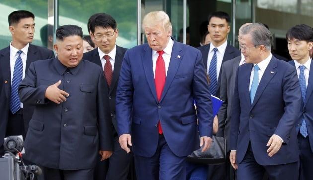 문재인 대통령, 도널드 트럼프 전 미국 대통령, 김정은 북한 국무위원장이 2019년 6월 30일 판문점 남측 자유의 집에서 군사분계선으로 이동하고 있다. 북한 화보집이 의도적으로 배제한 문 대통령은 트럼프 전 대통령의 오른편에 있다./ 연합뉴스
