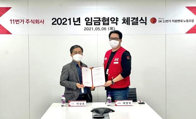 이상호 11번가 사장(왼쪽)과 예병학 노조 위원장이 임금 인상 합의안에 서명한 뒤 기념촬영을 하고 있다. 11번가 제공