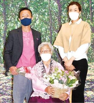 한진 소속 택배기사 이현영 씨(52)와 그의 어머니 김두엽 씨(94)의 그림 전시회 '우리 생애의 첫 봄'이 6일 서울 서소문동 일우스페이스에서 개막했다. 낮에는 택배기사로 일하며 틈틈이 그림을 그려온 이씨와 83세에 그림을 그리기 시작한 김씨의 작품 150여 점이 오는 30일까지 전시된다. 조현민 한진 부사장(오른쪽)이 축하행사에서 김씨(가운데)에게 꽃다발을 전달한 뒤 기념촬영을 하고 있다.  /신경훈 기자