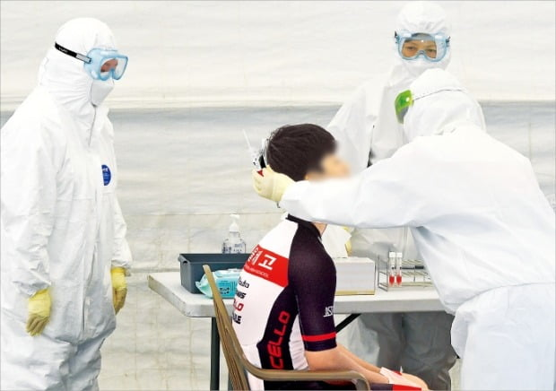 지난 3일 서울 송파구 서울체육중·고에 설치된 코로나19 이동식 PCR 검사소에서 한 학생이 검사를 받고 있다.   사진공동취재단