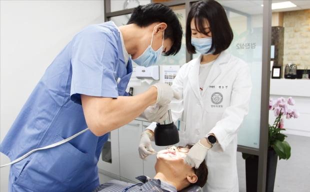 경희대치과병원 치과종합검진센터 의료진이 치아 형광분석검사를 하고 있다.  경희의료원 제공