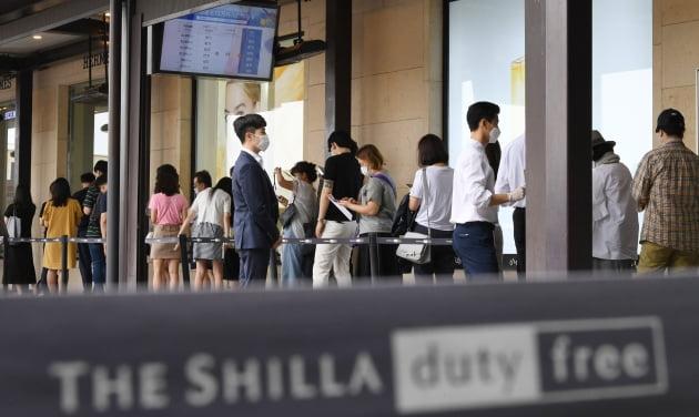 (사진) 소비자들이 2020년 7월 21일 서울 중구 신라면세점에서 재고 면세품을 구매하기 위해 줄지어 서있다. /김범준기자 bjk07@hankyung.com
