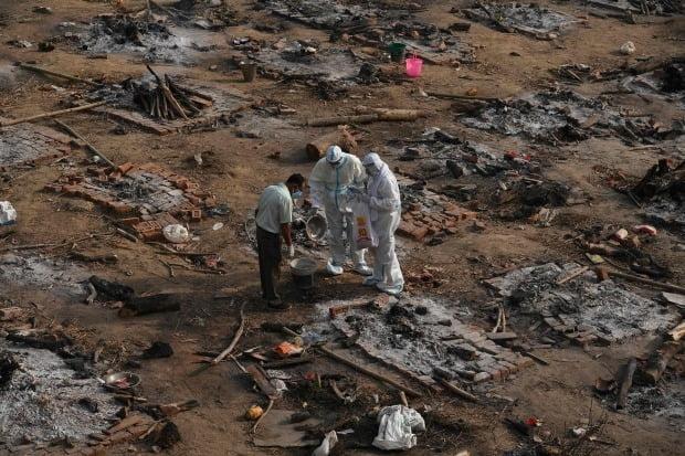 인도 수도 뉴델리의 노천 화장장에서 유족들이 화장한 신종 코로나바이러스 감염증(코로나19) 사망자 유해를 거두고 있다. /연합뉴스