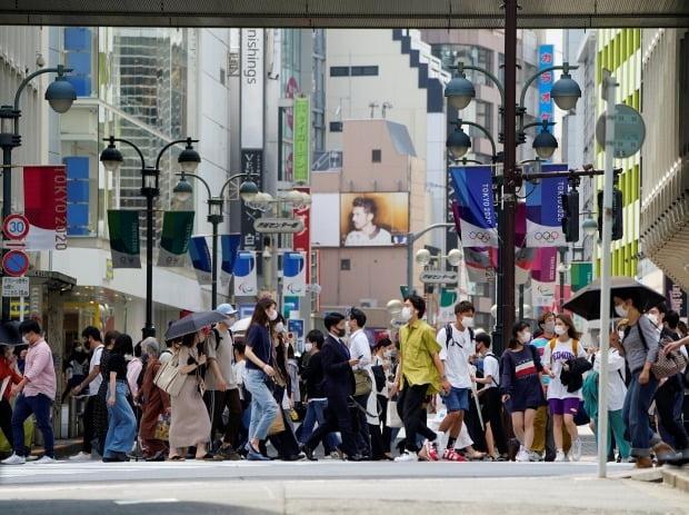 일본이 신종 코로나바이러스 감염증(코로나19) 확산으로 비상인 가운데 14일 수도 도쿄에서 행인들이 도쿄올림픽·패럴림픽 깃발로 장식된 거리를 걷고 있다. 사진=연합뉴스