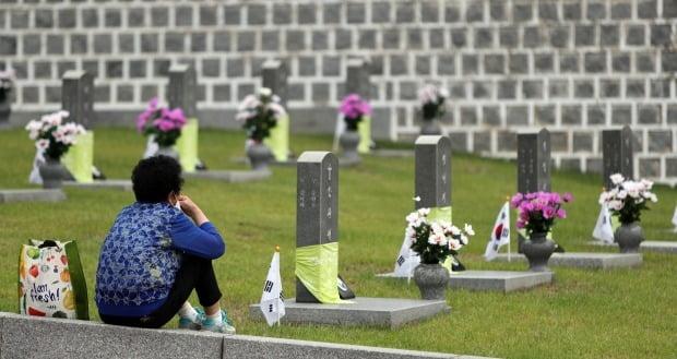 5·18 민주화운동 41주년을 맞은 지난 18일 광주 북구 운정동 국립 5·18민주묘지에서 유가족이 묘소 앞에 앉아있다. /사진=연합뉴스