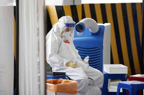 지난 11일 오전 광주 북구선별진료소에서 신종 코로나바이러스 감염증(코로나19) 검사를 하는 보건소 의료진이 얼린 생수통을 손에 들고 잠시 더위를 식히고 있다. 연합뉴스
