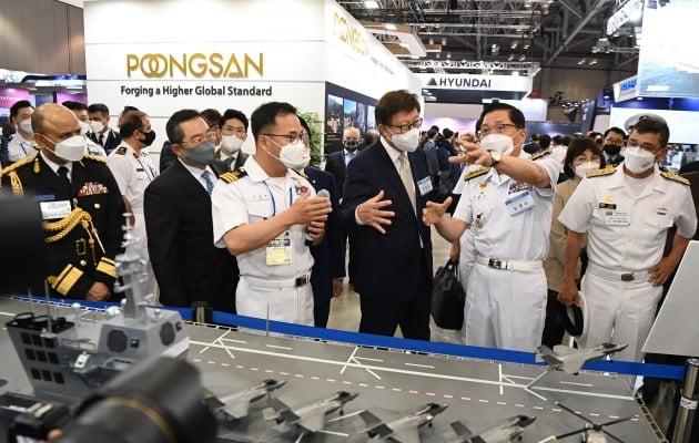 김정수 해군참모차장(오른쪽 두번째)이 지난 9일 부산 벡스코에서 '국제해양방위산업전(MADEX 2021)' 해군 홍보관에서 박형준 부산시장 및 외국 군 관계자들에게 경항공모함에 대해 설명하고 있다./ 해군 제공
