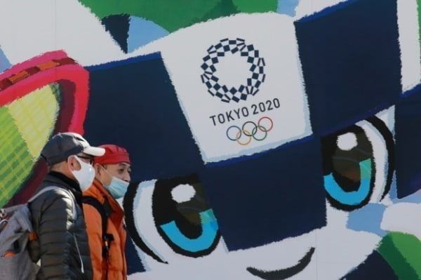 도쿄에서 시민들이 도쿄올림픽·패럴림픽 홍보 포스터 앞을 지나가고 있다/사진=AP