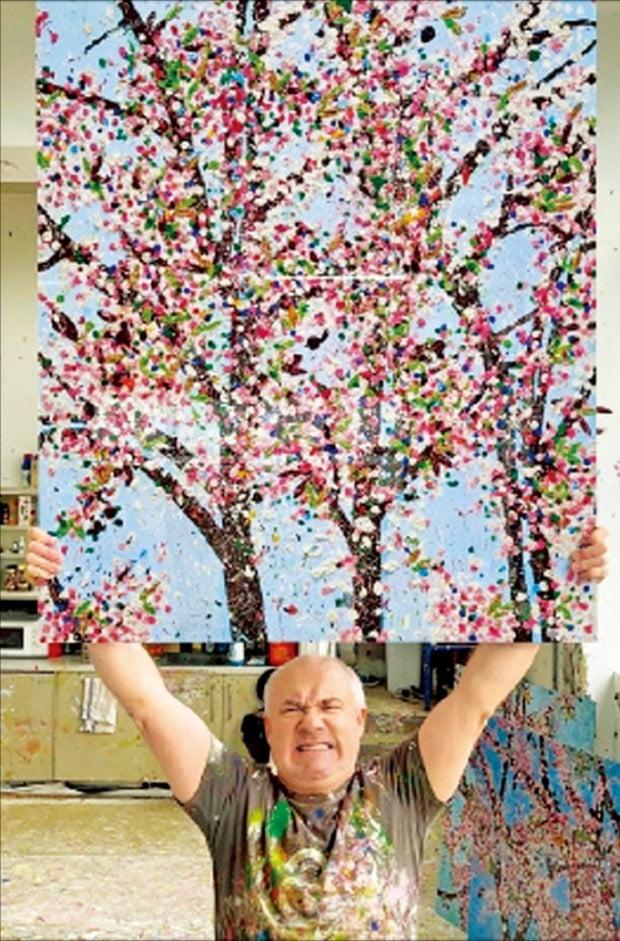 최근 자신의 그림을 NFT(대체 불가능 토큰)로 판매하겠다고 밝힌 영국의 세계적인 화가 데이미언 허스트가 벚꽃을 그린 작품을 들고 있다. /데이미언 허스트 트위터