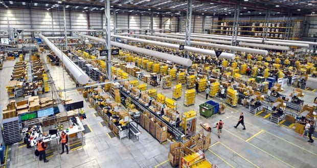 영국 피터보로에 있는 아마존 물류창고에서 직원들이 물건을 옮기고 있다. 아마존은 미국 시장 점유율 약 40% 등 세계 전자상거래 시장에서 독보적 위치를 차지하고 있어 미국 의회가 최근 독점 규제법 등으로 규제하는 방안을 추진 중이다.  AFP연합뉴스