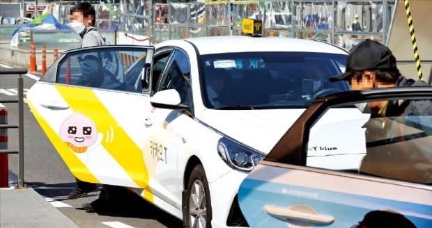 운송 플랫폼 브랜드인 카카오T 블루 택시에서 손님이 내리고 있다. 국토교통부에 따르면 지난 4월 기준 카카오T 블루, 마카롱택시, 반반택시그린, 우버택시 등 플랫폼 형태의 브랜드 택시는 약 3만 대가 운행 중이다.   연합뉴스