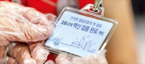 한 시민이 17일 서울 영등포구가 발급한 코로나 백신접종 완료 카드를 살펴보고 있다.   /연합뉴스